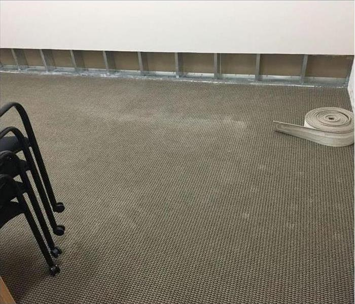 Wet walls cut and removed and carpet is dried in large conference room.