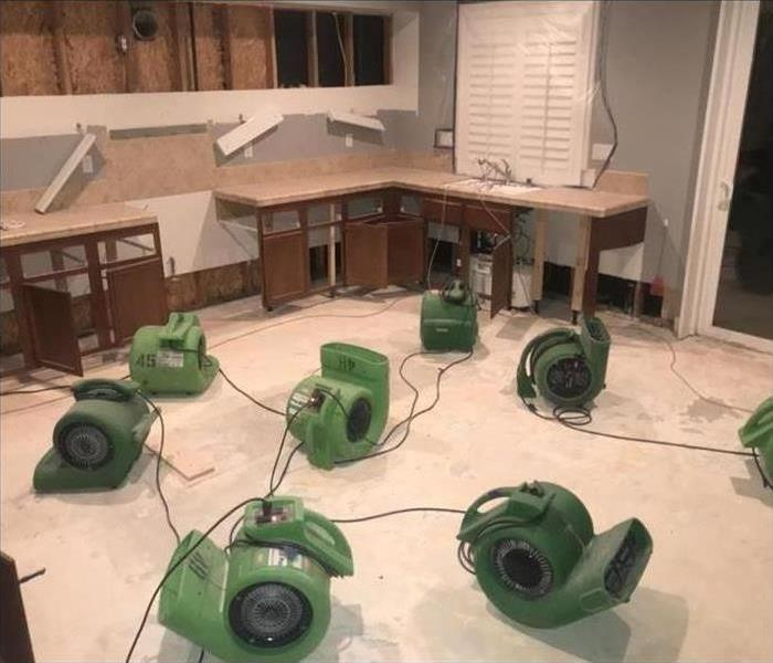Wood flooring removed in kitchen and machines placed to dry.