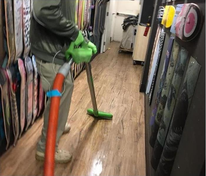 Employee with extraction machine removing water from mall floor.
