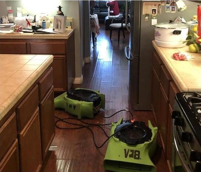 Water on wood flooring with machines.