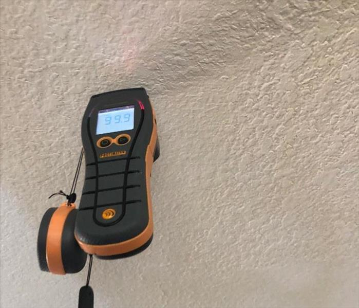 Moisture meter detecting water levels in dry wall.