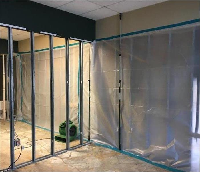 Walls of an office removed and containment was put up.