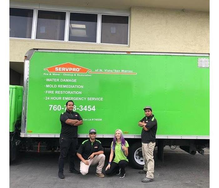 Three men and a lady standing in front of a green work truck.