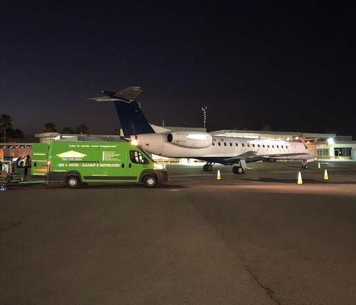 Green truck parked next to airplane on tarmac.