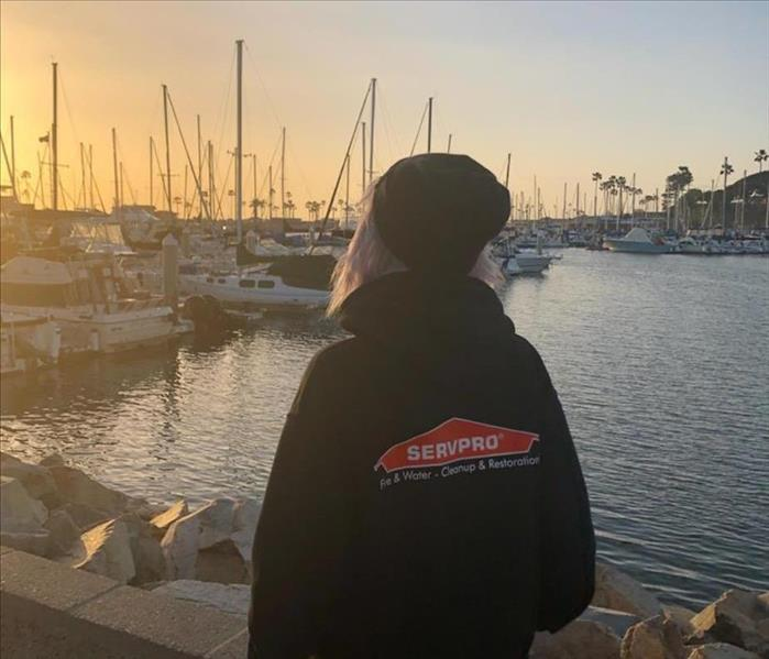 Woman wearing black SERVPRO hoodie while looking into the bay docked with boats.