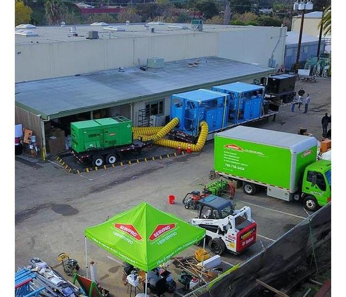 Aerial view of a job with green trucks and green generator.