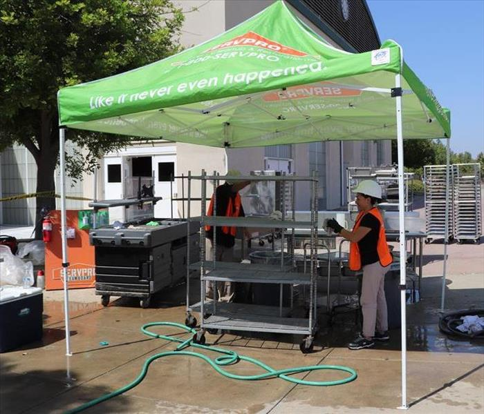 Crew cleaning contents at a middle school under a SERVPRO easy up.