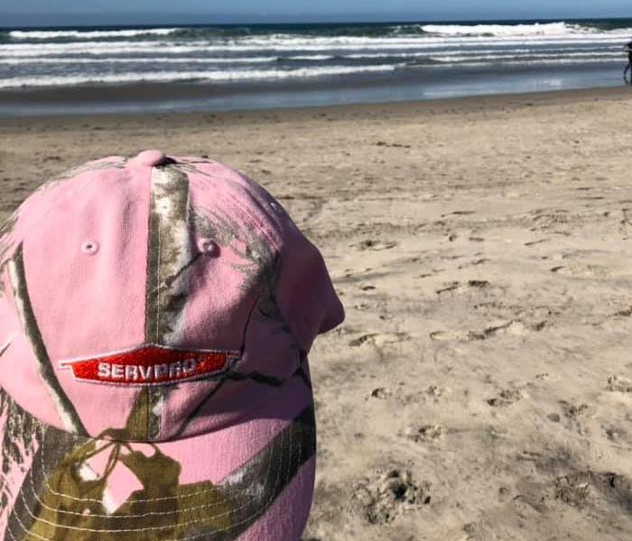 Pink SERVPRO hat in front of the beach.