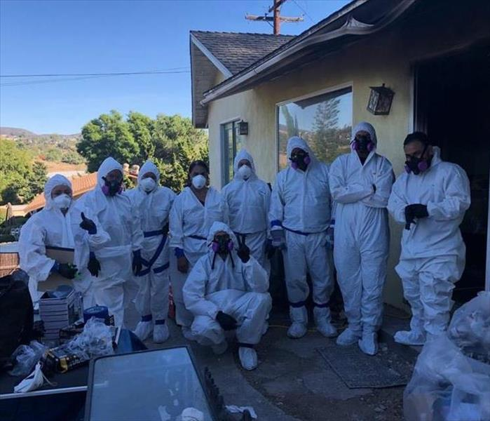 Team memebers suited in white personal protective equipment as house fire.
