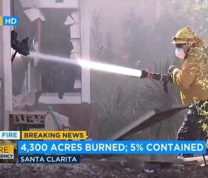 Screenshot of news displaying firefighter putting wildfire out with hose.